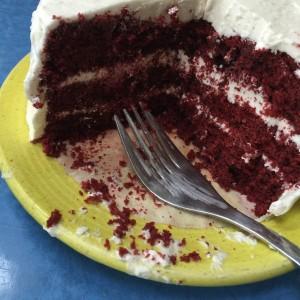 Cake fork resting on cake plate, partially eaten cake